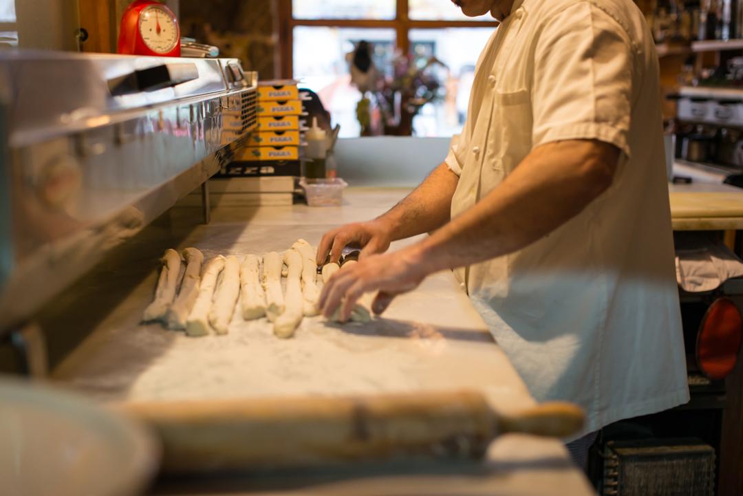 Pizzero preparando pan casero en horno de leña