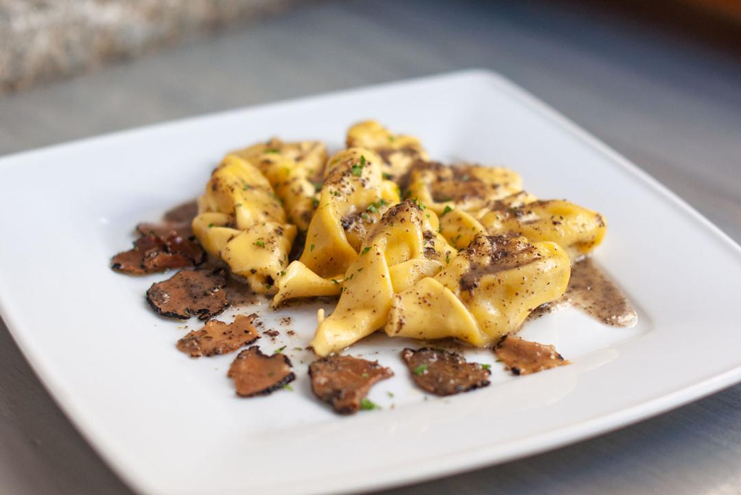 Ravioli Tartufo - Pasta rellena de parmesano y trufa con salsa de trufa.